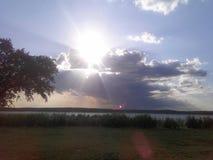 Solen som döljer bak molnen över en Texan sjö arkivbild