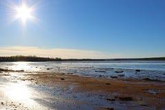 Solen som går ner över gyttjalägenheter på lågvatten i en saltvattens- fjärd på kusterna av Nova Scotia i vår royaltyfria foton