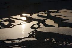 Solen ställer in över de storartade travertinesna, annorlunda bekant som bomullsslott på Pamukkale i Turkiet royaltyfri foto