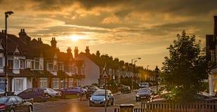 Solen ställer in över en gata av terrasshus i Croydon, London Royaltyfri Foto