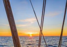 Solen ställer in över horisonten i havet Beståndsdelar av riggning arkivbilder