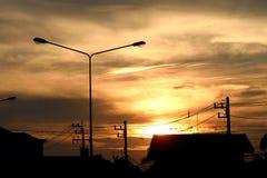 Solen ställer in bak byn i Thailand arkivbilder