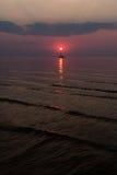 Solen ställer in i havet på bakgrunden av yachter Fotografering för Bildbyråer
