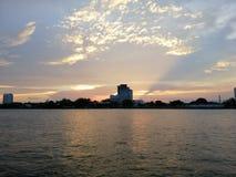 Solen ställer in på bankerna av Chao Phraya River - Wat Kretkrai, Bangkok-Thailand arkivbild