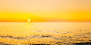 Solen ställer in på horisont på solnedgångsoluppgång över havet eller havet Royaltyfri Bild