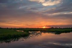 Solen ställer in på horisonten av den holländska bygden En härlig kulör himmel reflekteras i vattnet av en sjö royaltyfria foton