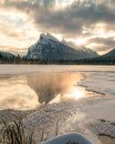 Solen stiger över cinnoberfärg sjöar med Mt Rundle Royaltyfri Bild