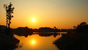 Solen stiger upp med reflexionen av sjön royaltyfri foto