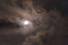 Solen under en partisk sol- förmörkelse med mörka moln Arkivbild