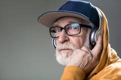 Solenny nieogolony stary człowiek z słuchawkami obrazy stock
