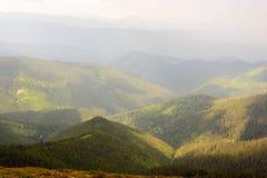Solens strålar i de Carpathian bergen efter regn Arkivbild