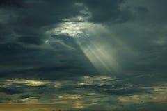 Solens str?lar p? solnedg?ngen som g?r deras v?g till och med molnen royaltyfria foton