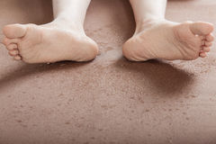 Soles of dirty feet on ground. Close up view on soles of dirty feet from unidentifiable person laying on his back over the floor with copy space Royalty Free Stock Photography