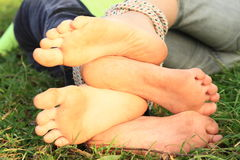 Soles of girls´ bare feet. Four soles of tied bare feet of two little girls playing on grass stock image