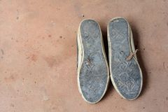the soles of  old sport shoes on dirty cement ground Stock Photo