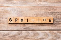 Soletrando a palavra escrita no bloco de madeira soletrando o texto na tabela de madeira para seu desing, conceito imagens de stock royalty free
