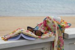 Solglasögon, bok och halsduk Arkivbilder