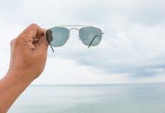 Solglasögon för hand för man` s hållande på havet på stranden Arkivbilder