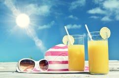 Solglasögon, hatt och fruktsaft Arkivbild