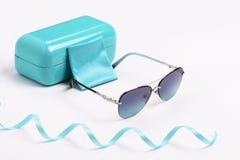 Solglasögon med blåa linser i sammansättning med det blåa fallet på en vit bakgrund royaltyfri bild