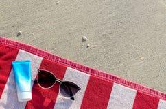 Solglasögon med den sunscreenlotion och påsen på den röda handduken royaltyfri bild