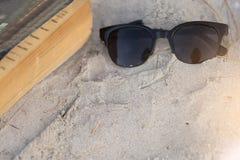Solglasögon med textboken på sandstranden fotografering för bildbyråer