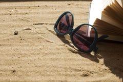 Solglasögon och bok på sand Fotografering för Bildbyråer