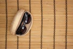 Solglasögon och fall på träbakgrund royaltyfria bilder