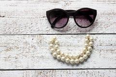 Solglasögon och halsband arkivbilder