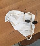 Solglasögon och vit påse i trätabell arkivbild