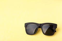 Solglasögon på den gula trätabellen Royaltyfri Bild