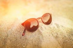 Solglasögon på den guld- sanden med reflexioner i exponeringsglaset Seascapehav och härligt strandparadis Resa resväskan med seas Arkivfoton