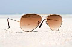 Solglasögon på en sandstrand Fotografering för Bildbyråer