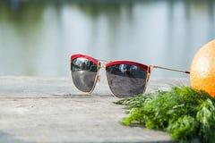 Solglasögon på en trätabell Fotografering för Bildbyråer