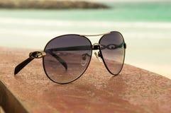 Solglasögon på ett träskrivbord arkivbild