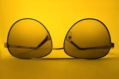 Solglasögon på gul bakgrund arkivbilder