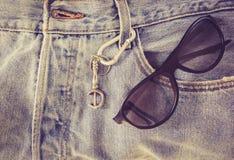 Solglasögon på jeanflåsanden Arkivfoton