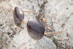 Solglasögon på jordningen Arkivbilder