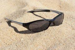 Solglasögon på sand Arkivfoton
