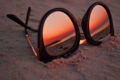 Solglasögon på sanden med solnedgången royaltyfri foto