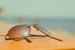 Solglasögon på tabellen nära havet Arkivfoto