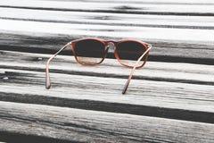 Solglasögon på trägolv Arkivfoto