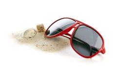 Solglasögon, sand och skal arkivfoto