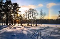 Solgloria på den snöade sjön Arkivfoto