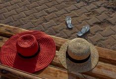 Solhattar på en bänk och att bläddra misslyckanden utan ägaren royaltyfri foto