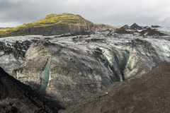 Solheimajokull glacier covered with black volcanic ash with blue cleft and group of hiking people, Iceland Stock Images