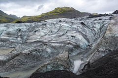 Solheimajokull glacier covered with black volcanic ash with blue cleft, Iceland Stock Image