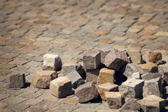 Solid as a rock. Cubic rocks in random order over a pavement made from the same Royalty Free Stock Image
