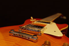 Solid body electric jazz guitar closeup on black background. Selective focus. Stock Photo