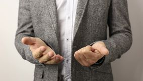Solid caucasian man in gray jacket and speckled shirt on white background slowly counting unbending fingers till ten
